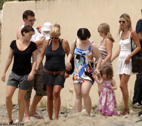 A PHOTO OF KATE MOSS AND ENTOURAGE OF FRIENDS IN IBIZA